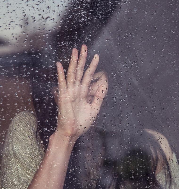 執着心を捨てる方法 恋愛 雨のついたガラスに向かって手を置き泣いている女性